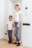 Mutter und Sohn halten sich an den Händen und blicken in die Kamera neben der Tür im Flur