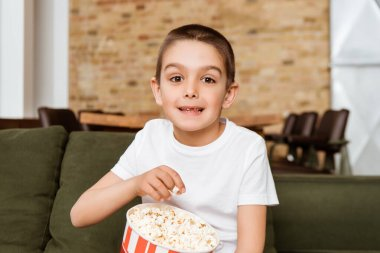 Smiling child looking at camera while eating popcorn on couch stock vector