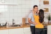 mladá žena objímání bi-rasový přítel v kuchyni