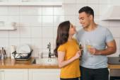 šťastný mezirasový pár drží brýle s bílým vínem doma