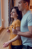cheerful interracial couple holding glasses with white wine at home