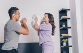 side view of cheerful interracial couple pillow fighting in bedroom