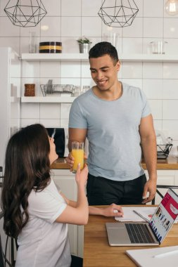 KYIV, UKRAINE - MAY 14, 2020: happy mixed race man giving glass of orange juice to girlfriend near laptop with ebay website stock vector
