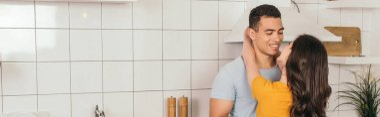 Panoramic orientation of girl hugging bi-racial boyfriend in kitchen stock vector
