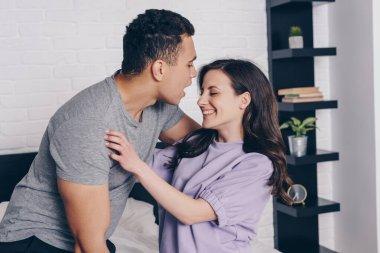 Bi-racial man hugging cheerful girl in bedroom stock vector