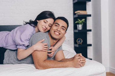 Cheerful woman with closed eyes hugging handsome bi-racial man while lying on bed stock vector