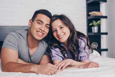 Cheerful and young multiracial couple smiling in bedroom stock vector