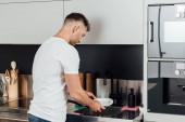 jóképű férfi álló és mosás nedves tál a konyhában