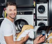 Fotografie Collage eines fröhlichen Mannes mit schmutziger Kleidung und Messbecher mit Waschmittel in der Nähe von Waschmaschinen
