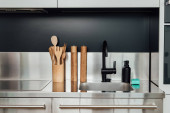 wooden pepper mill and salt mill near faucet, sink, soap dispenser and sponge in kitchen