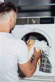 Mann legt schmutzige Wäsche in moderne Waschmaschine