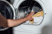 Ausgeschnittene Ansicht eines Mannes, der schmutzige Wäsche in die Waschmaschine legt