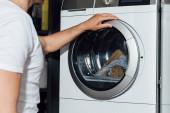 abgeschnittene Ansicht eines Mannes, der moderne Waschmaschine berührt