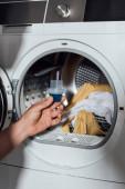 levágott kilátás az ember gazdaság mérőpohár kék mosószer közelében mosógép piszkos ruházat