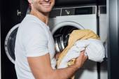 vágott kilátás boldog ember gazdaság piszkos mosás közelében mosógép
