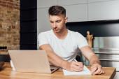 koncentrált férfi gazdaság toll és nézi laptop, míg az online vizsgálat