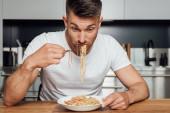 Mann isst leckere Nudeln am Küchentisch