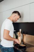 Oldalnézet jóképű férfi főzés tészta sütőben serpenyőben a konyhában