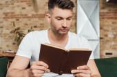 Selektivní zaměření pohledný muž čtení knihy doma