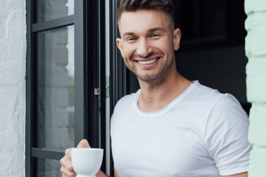 Selective focus of handsome man smiling at camera while holding cup of coffee near terrace door stock vector