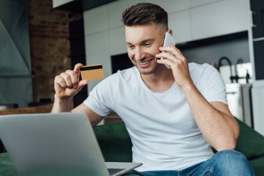 Selective focus of smiling man holding credit card while talking on smartphone near laptop in living room stock vector