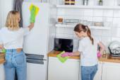 sestry v gumových rukavicích drží hadry při čištění kuchyně