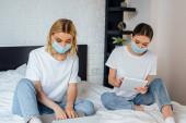 Nővérek orvosi maszkok segítségével laptop és digitális tabletta az ágyban