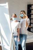 Fiatal nővérek orvosi maszkban a tükröt nézik a hálószobában.