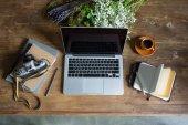 pohled shora na notebook, diáře, ročník fotografické kamery a šálek kávy na dřevěnou desku
