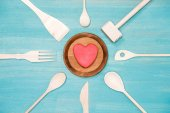 Fotografie pohled shora různé dřevěné kuchyňské náčiní symbolem srdce na talíři
