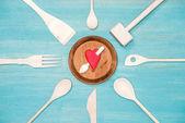 Fotografie pohled shora různých dřevěných kuchyňských potřeb s propíchnuté srdce symbol na štítku