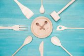 Fotografie pohled shora různých dřevěných kuchyňských potřeb se symbolem hodin na desce