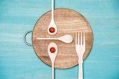 Fotografie pohled shora dřevěné kuchyňské náčiní s rajčaty v podobě tváře na kuchyňské desce