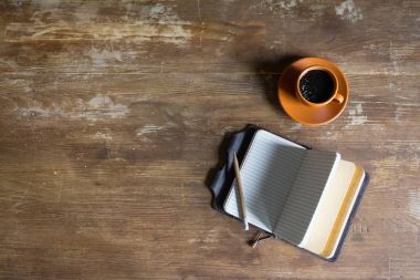 top view of diary with pencil and coffee cup on wooden tabletop