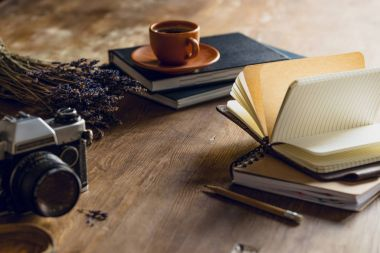 Vintage photo camera, and diaries and cup of coffee on wooden tabletop stock vector