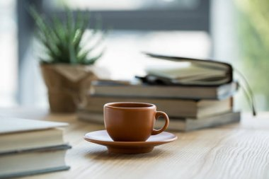 Close-up view of cup of coffee and notebooks on wooden table top