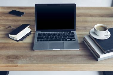 Close-up view of open laptop with blank screen and cup of coffee at workplace