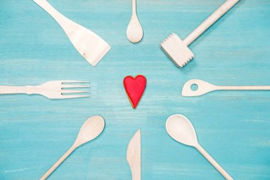 top view of various wooden cooking utensils with heart symbol on blue tabletop