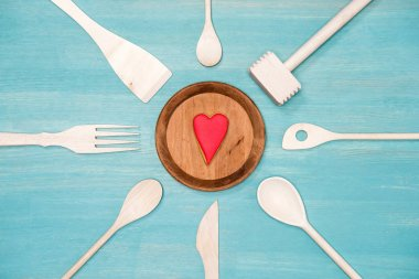 top view of various wooden cooking utensils with heart symbol on plate