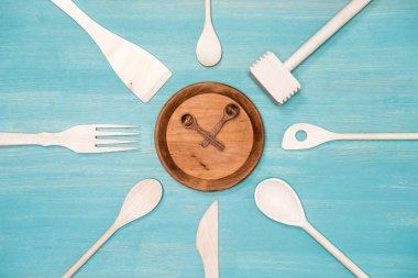 top view of various wooden kitchen utensils with clock symbol on plate