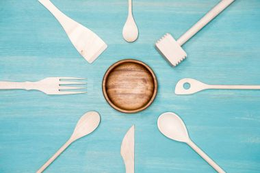 top view of various wooden cooking utensils with plate