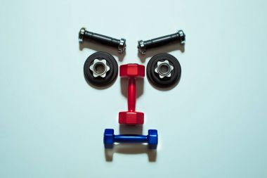 Top view of various dumbbells and weight plates in shape of serious face