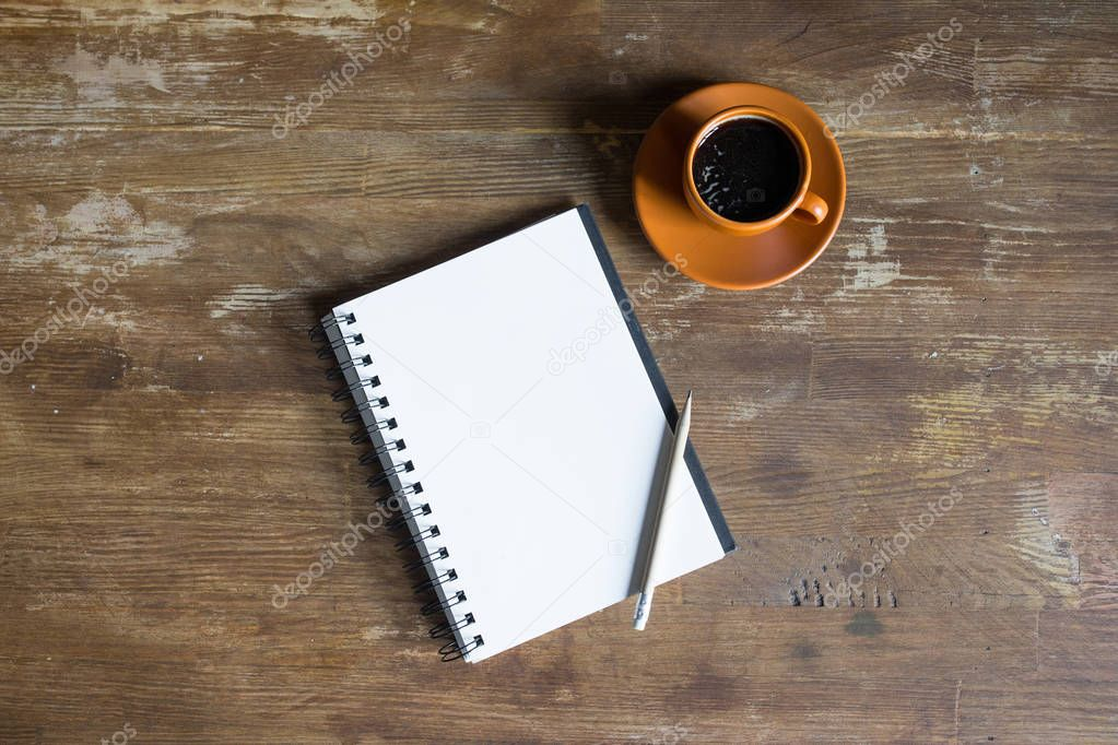 top view of notepad with pencil and coffee cup on wooden tabletop