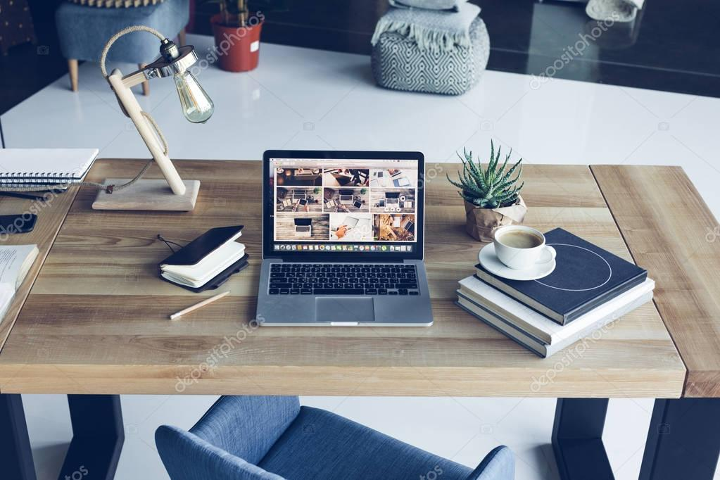 Open laptop, books and cup of coffee at modern workplace