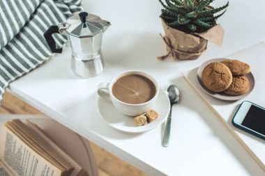 coffee with cookies and potted plant on tabletop