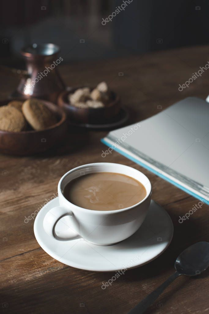coffee cup with empty book on tabletop