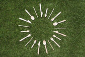 wooden spoons with forks and knives on grass