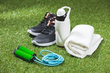 trainers with bottle of water and towel on grass