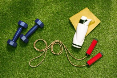 dumbbells and bottle with jump rope on grass