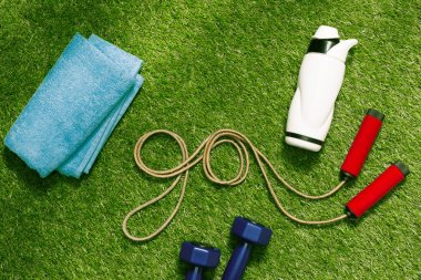 towel and bottle with jump rope on grass